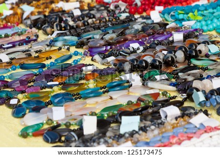 Bracelets and necklaces made of natural gems at store - stock photo
