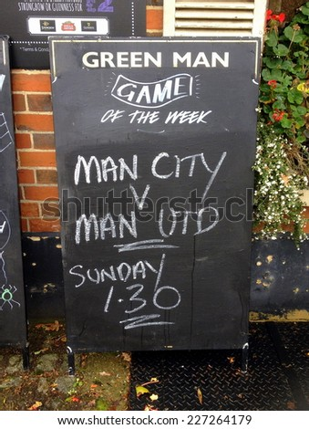 Bracknell, United Kingdom - October 31, 2014: Blackboard sign outside The Green Man Public House advertising TV coverage of the Manchester United and Manchester City Premier League Football match  - stock photo