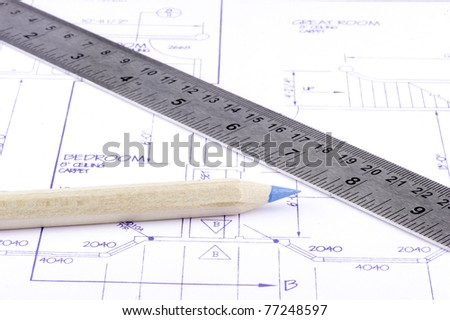 Brad bit in a drill laying on a set of commercial building plans with a pencil and ruler - stock photo
