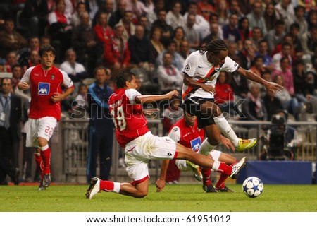 BRAGA, PORTUGAL - SEPTEMBER 28: Shakhtar Donetsk's (UKR) forwarder Willian (R) dribles through Vandinho (M), Braga's (POR) defender, in UEFA Champions League on September 28, 2010 in Braga, Portugal - stock photo