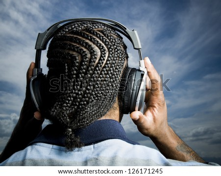 Braided hair of African American man holding headphones - stock photo