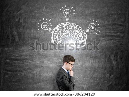 Brain and three bulbs drawn on black chalkboard. Man with hand in chin in front. Concept of mental activity. - stock photo