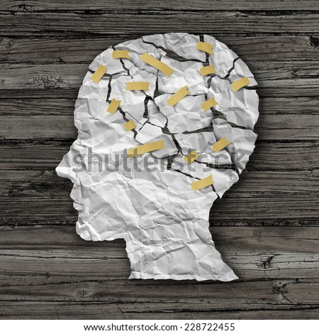 Brain disease therapy and mental health treatment concept as a sheet of torn crumpled white paper taped together as a human face on wood as a symbol for neurology surgery  or psychological help. - stock photo