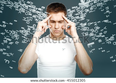 Brainstorming concept with pensive young man surrounded with abstract letters on grey background - stock photo