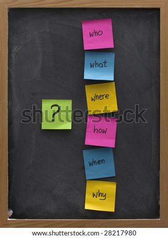 brainstorming concept with simple questions (what, when, where, why, how, who)  posted with colorful sticky notes on blackboard with white chalk smudges