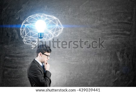 Brainstorming concept with thoughtful businessman standing against chalkboard with illuminated polygonal brain sketch and abstract light bulb - stock photo