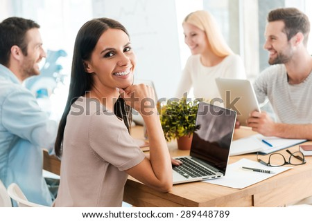 Brainstorming with colleagues. Beautiful young woman holding hand on chin and smiling while sitting together with her colleagues at the desk in office  - stock photo