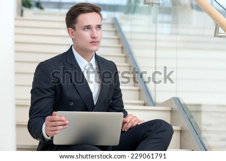 Brainstorming. Young and successful businessman is sitting with laptop and thinking about good business solution - stock photo