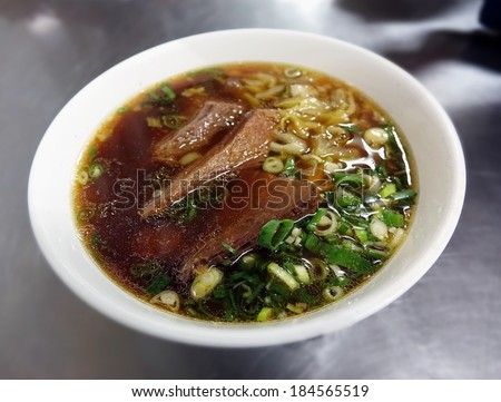 Braised beef in broth with noodles and chives is a popular dish in Taiwan - stock photo