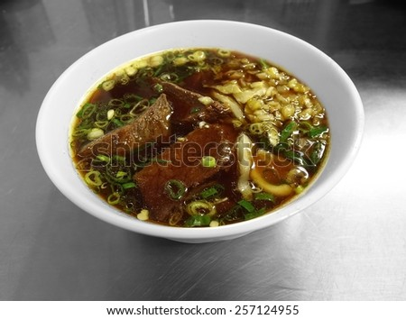 Braised beef in broth with thick noodles and chives is a popular dish in Taiwan - stock photo