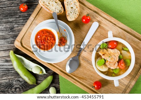 Braised chicken things with new potatoes, tomatoes and butter lima bean in gratin dish and in soup bowl on table mat, tomato and bell pepper sauce in gravy boat, view from above - stock photo