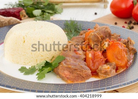 Braised lamb with dried apricots and couscous - stock photo