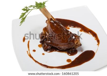 Braised leg of lamb in sauce. - stock photo