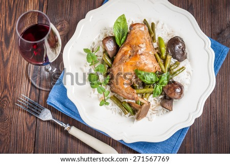 braised rabbit leg with mushrooms, green beans and basmati rice on a white plate. Dinner/lunch with a glass of red wine. - stock photo