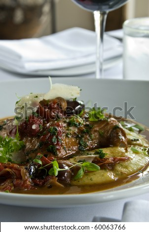 Braised rabbit over polenta with red peppers - stock photo
