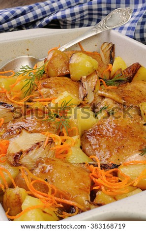 Braised roast chicken with potatoes, carrots and shalott in ceramic roasting pan