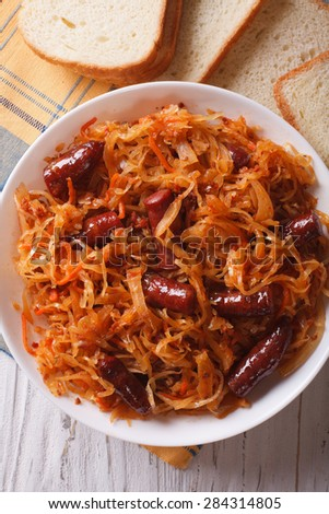 braised sauerkraut with sausages close-up in white plate. vertical top view - stock photo