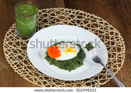 Braised spinach,  poached egg and green smoothie - stock photo