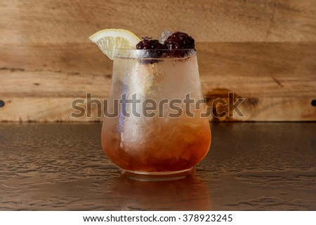 Bramble is a cocktail that contains gin, blackberry liqueur, lemon juice and simple syrup - stock photo