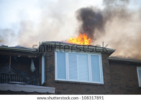 BRAMPTON, ONTARIO -  JULY 20 2012 - Flames shoot from the roof of a house fire at 20 Esker Drive in Brampton Ontario on July 20, 2012 - stock photo