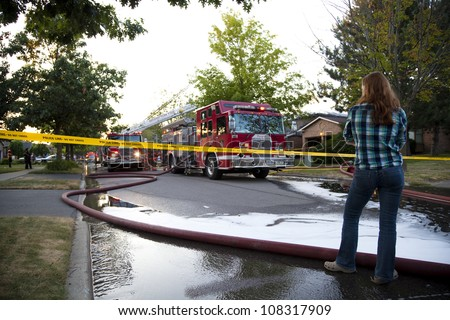BRAMPTON, ONTARIO -  JULY 20 2012 - Teen girl stands behind police tape watching a house fire at 20 Esker Drive in Brampton Ontario on July 20, 2012 - stock photo