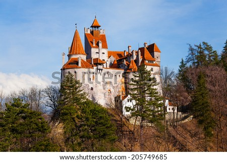Bran Castle among trees on hill in Romania