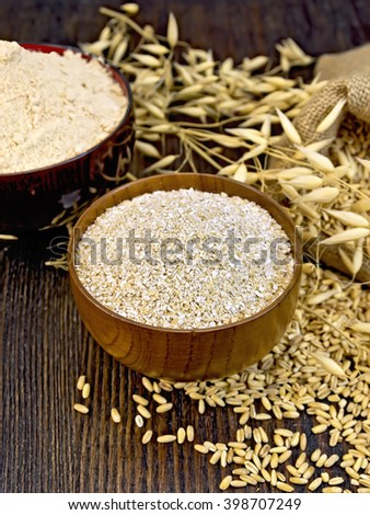 Bran flakes and oat flour in two wooden bowl, a bag of grain oaten, ears on background of wood boards