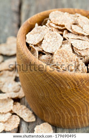 bran flakes in a wooden bowl on wooden table
