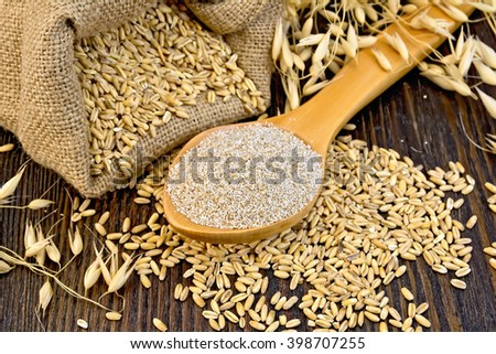 Bran flakes oat in spoon, a bag of grain oaten, ears on the background of wooden boards