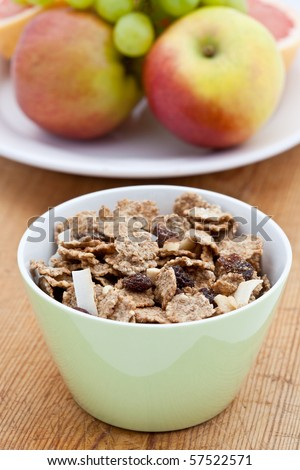 Bran flakes with a bowl of fruit in the background - stock photo