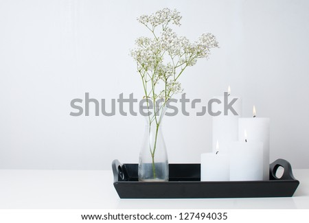 Branch in a vase, and four white candles burning on a black tray on a white table in an interior - stock photo