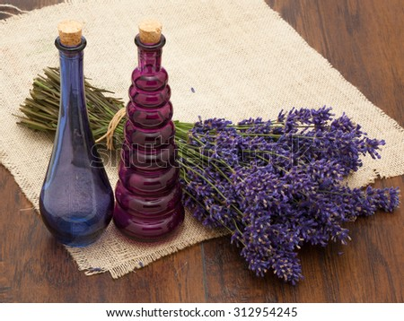 Branch of a lavender and vintage bottles on a wooden background.  - stock photo