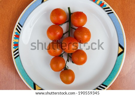 Branch of cherry tomatoes on plate
