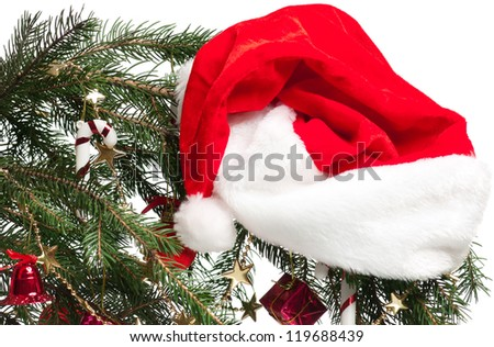 Branch of Christmas fur-tree with Santa claus red hat over white - stock photo