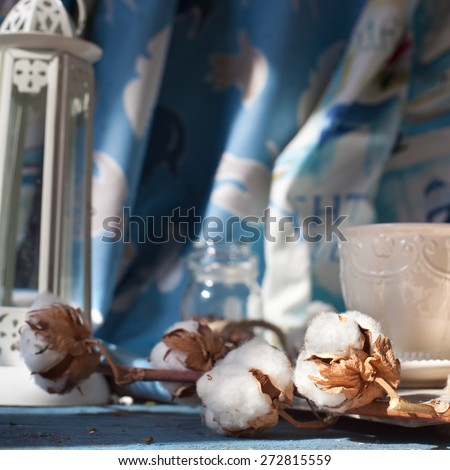 Branch of cotton flowers set with home decorations: cotton fabrics, cup of coffee and a lighthouse candle holder, shot in natural daylight. Marine style home decorations and sea holiday concept. - stock photo