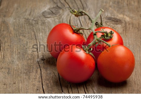 Branch of fresh tomato on old wooden table - stock photo