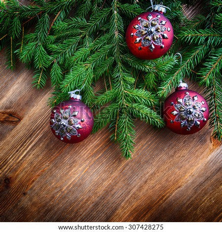 branch of green fir tree with christmas toys on wooden background - stock photo