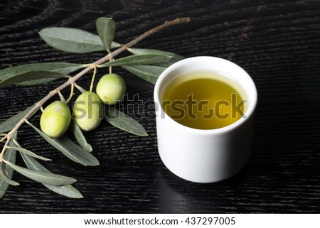Branch of olive tree with green olive berries and cap of fresh olive oil on a black wooden table or board. Selective focus. - stock photo