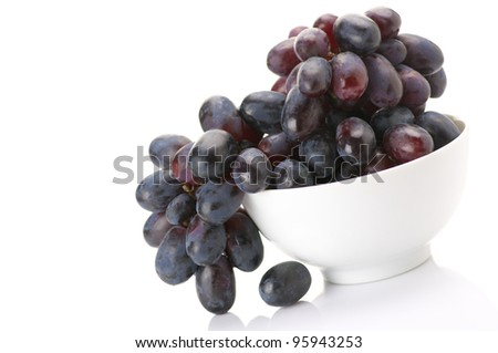 Branch of purple grape in white bowl isolated on white background. - stock photo