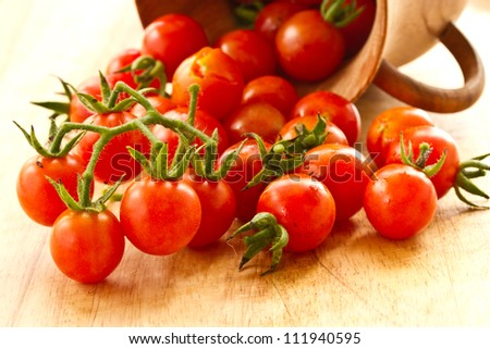 branch of red ripe cherry tomatoes on a wooden board - stock photo