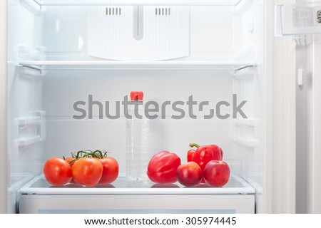 Branch of red tomatoes, two red peppers, two two-colored orange and red peaches and a bottle of water on shelf of open empty refrigerator. Weight loss diet concept. - stock photo