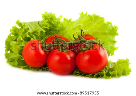 Branch of tomatoes on salad leaf isolated on white background