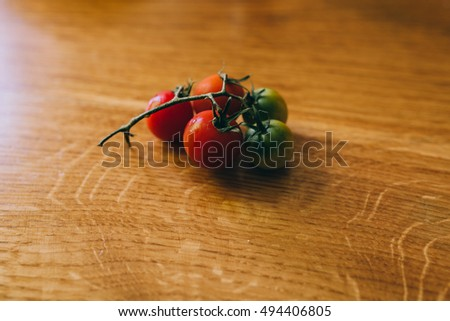 branch of tomatoes on wooden table