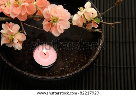 Branch quince and candle with water in bowl on stick straw mat - stock photo
