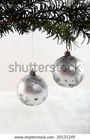 Branch with christmas ball on white snow