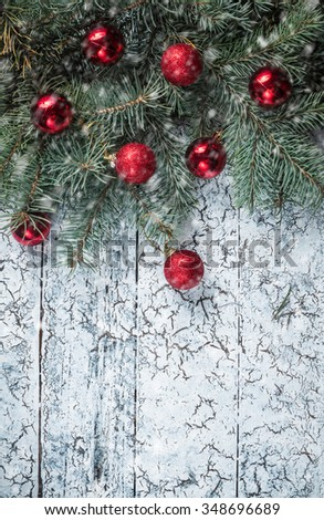 Branches of a Christmas tree on old boards. Christmas background. Christmas decorations. New Year background. Xmax background. Toned image. Falling Snow. - stock photo