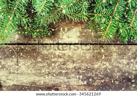 Branches of a Christmas tree on old boards. Christmas background. New Year background. Xmax background. Toned image. Falling Snow . - stock photo