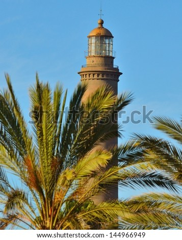 Branches of phoenix canariensis in foreground and stone lighthouse with splendid blue sky in background, Maspalomas, Gran canaria - stock photo