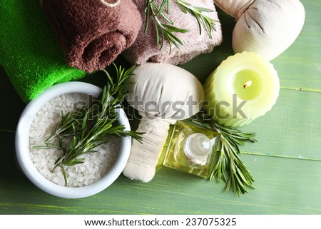 Branches of rosemary and sea salt in bowl, towels, candle and bottle with massage oil on color wooden background. Rosemary spa concept - stock photo