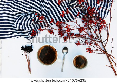 Branches with red berries hawthorn. and white cup of tea on white bakground, cup of tea with hip roses, on wooden table. Silver spoon. Hawthorn. Cup of herbal tea. Yellow autumn leaf. Cozy atmosphere. - stock photo